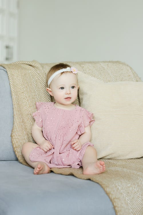 Girl in Pink Dress Sitting on Sofa