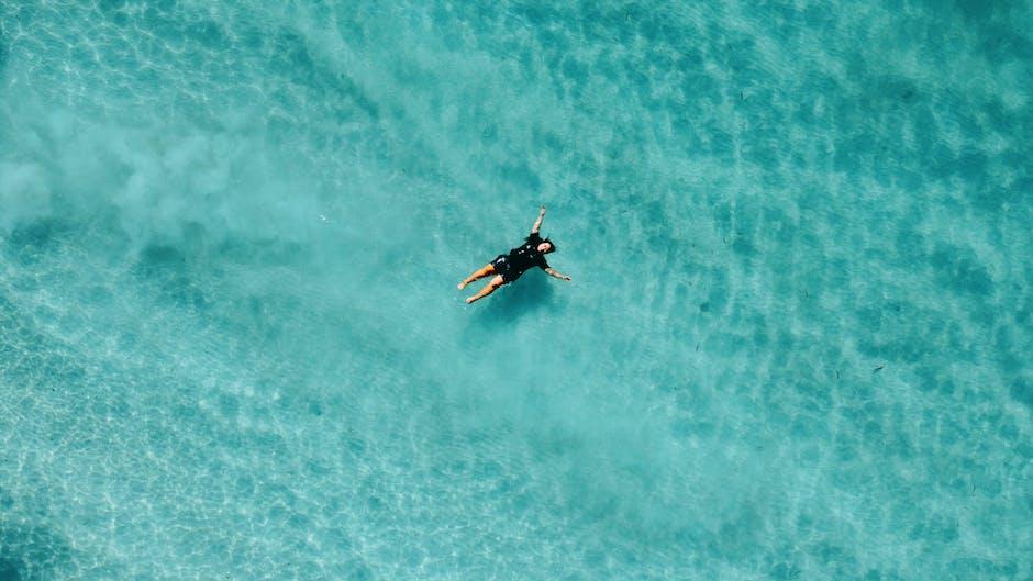 Person diving in blue sea