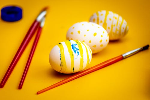Easter Eggs and Paint Brushes on Yellow Surface
