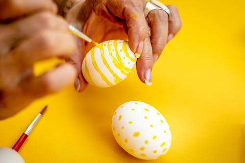 Person Decorating White Egg With Yellow Paint