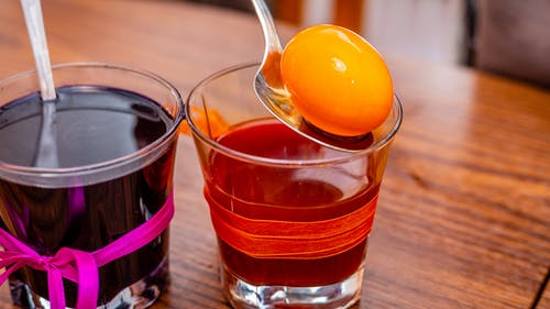 Two Clear Drinking Glasses With Colored Liquids on Wooden Surface