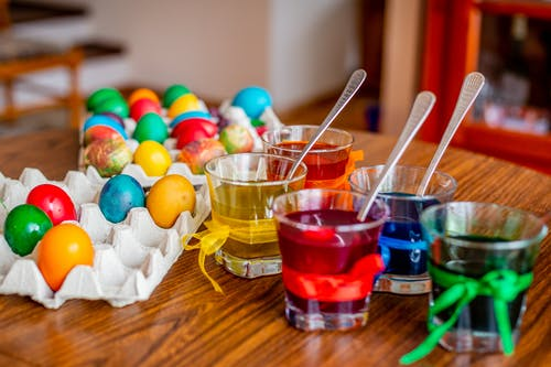 Clear Glasses With Colored  Liquids Beside Easter Eggs On Wooden Surface