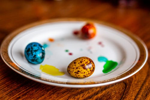 White Ceramic Plate With Easter Eggs on Wooden Surface