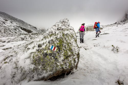 People Hiking On Mountain Covered With Snow