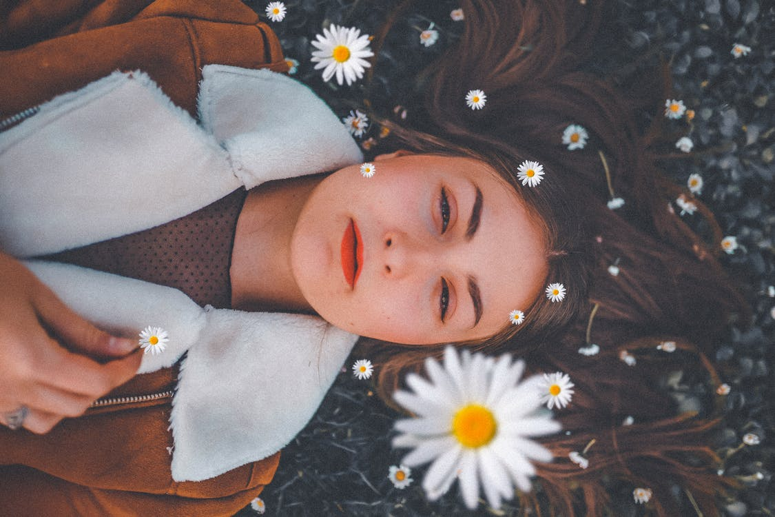 Woman Lying On Bed Of Flowers