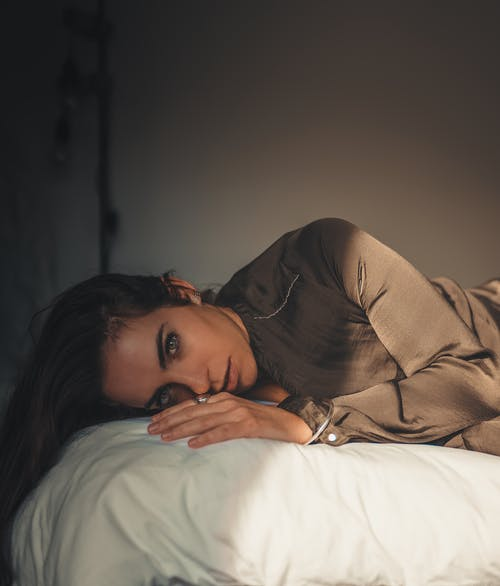 Woman in Brown Long Sleeve Shirt Lying on Bed