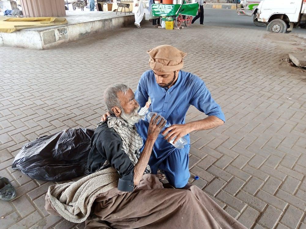 Man In Blue Clothing Feeding An Old Man