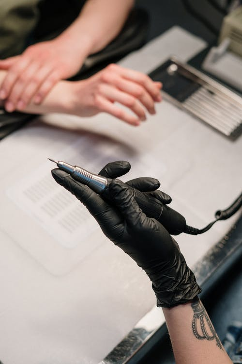 Person in Black Leather Gloves Holding Black Pen