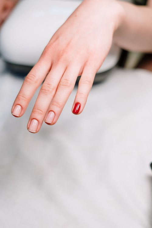 Person With Red Manicure on White Textile