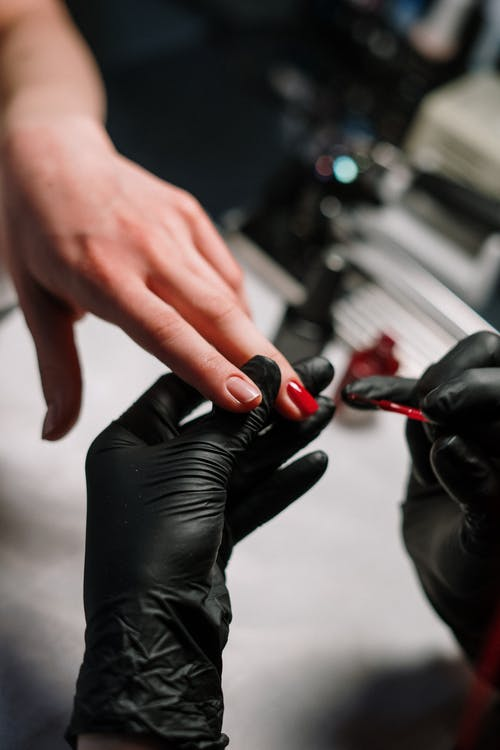 Person in Black Leather Gloves Holding Red Nail Polish