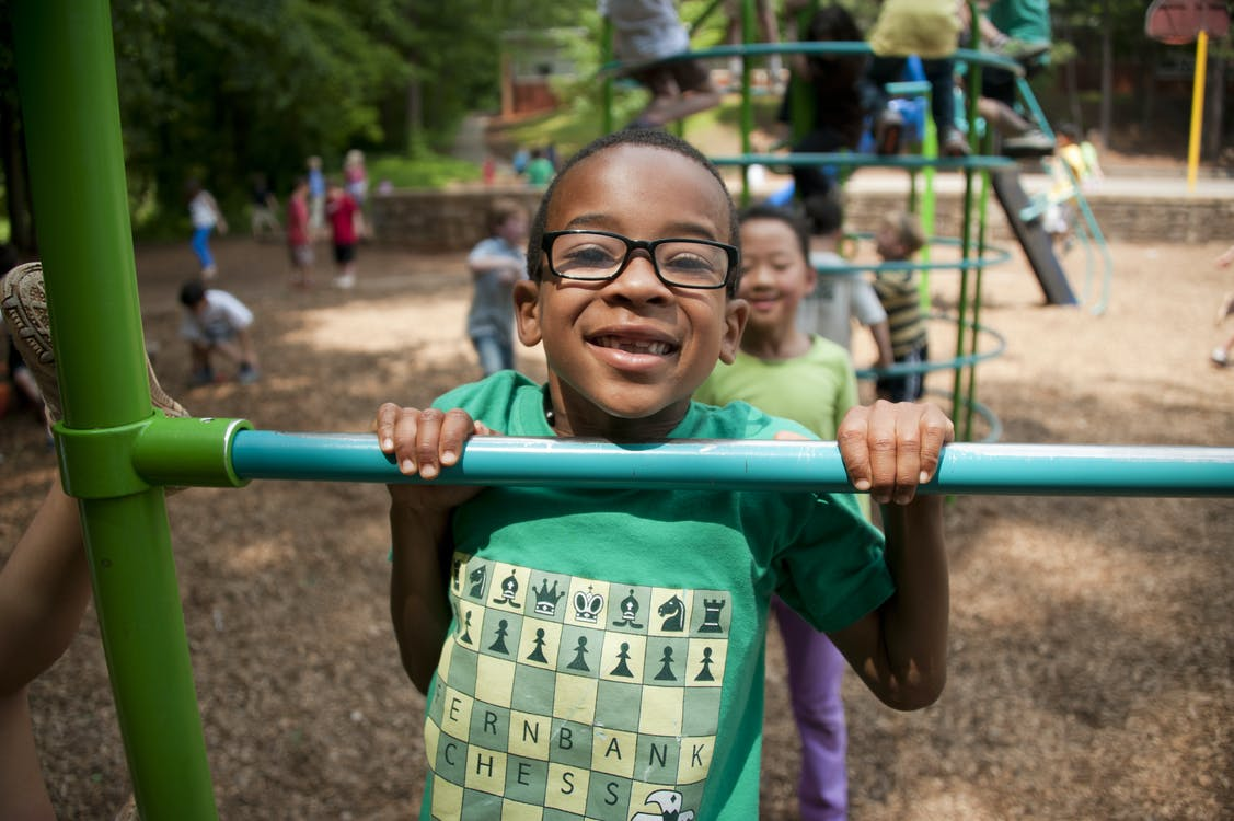Boy in Green Crew Neck T-shirt Wearing Black Framed Eyeglasses
