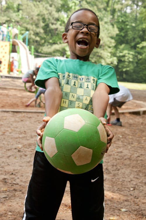 Boy in Green and White Crew Neck T-shirt Holding Yellow Soccer Ball