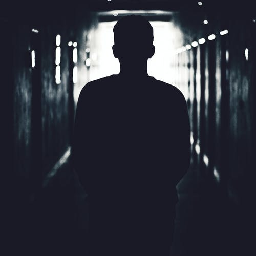 Silhouette of Man Standing on Hallway