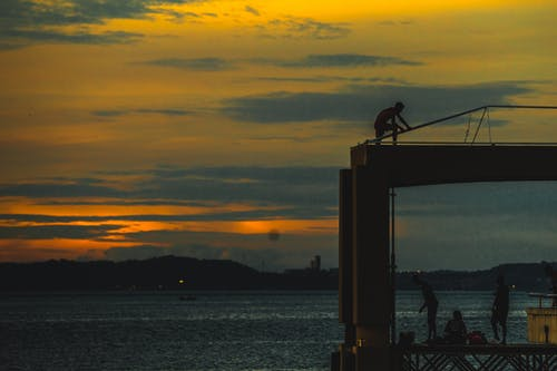 Silhouette of Man Standing on the Bridge during Sunset