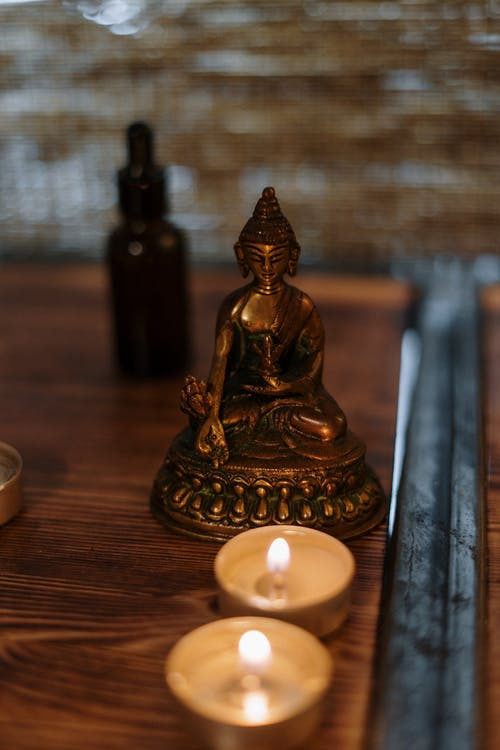 Gold Buddha Figurine on Brown Wooden Table