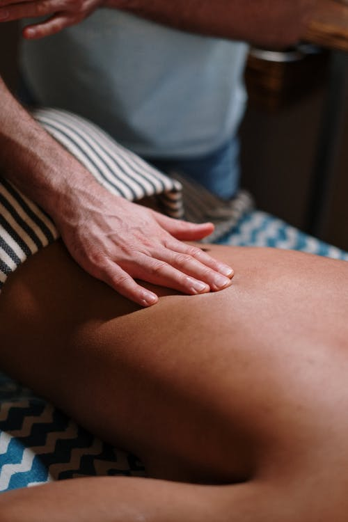 Woman Lying on Bed for a Massage