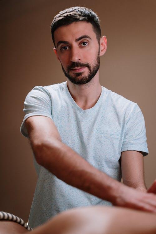 Man in White Crew Neck T-shirt Offering a Massage