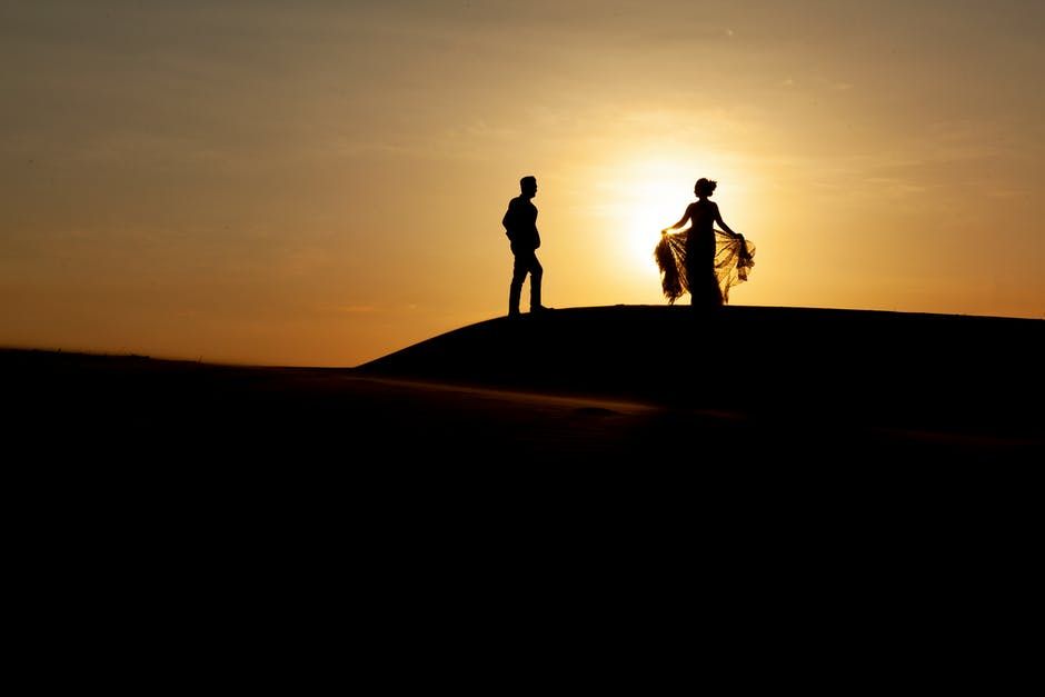 Silhouette of two people walking on sand during sunset
