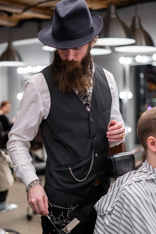 Man in Black Vest and White Long Sleeve Shirt Giving a Haircut