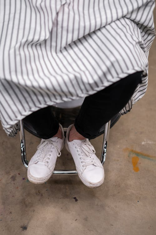 Person in White and Black Striped Shirt and Black Pants Wearing White Sneakers