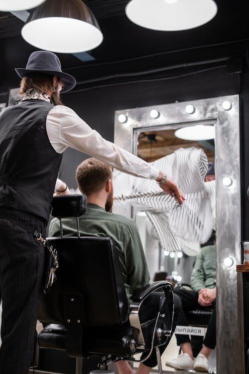 Man in Black Hat Cutting Hair of Man in Green Shirt