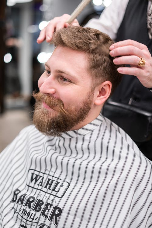 Man in White and Black Striped Veil Having a Haircut