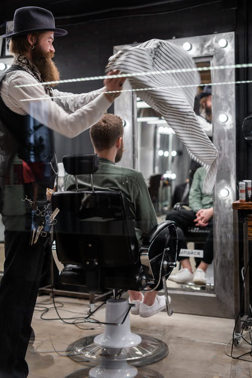 Man in Black Hat Giving a Haircut