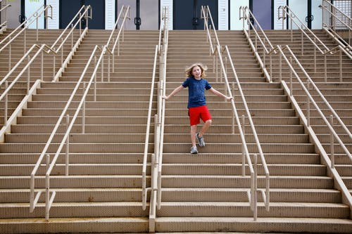 Boy in Blue T-shirt and Blue Shorts Walking on Gray Concrete Stairs