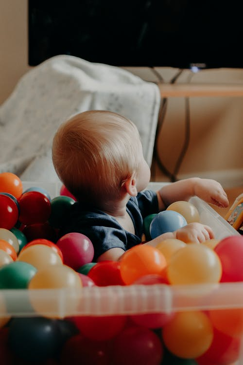 Baby in Blue and White Striped Shirt Playing With Orange Plastic Ball