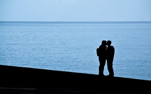 Couple Standing By The Sea