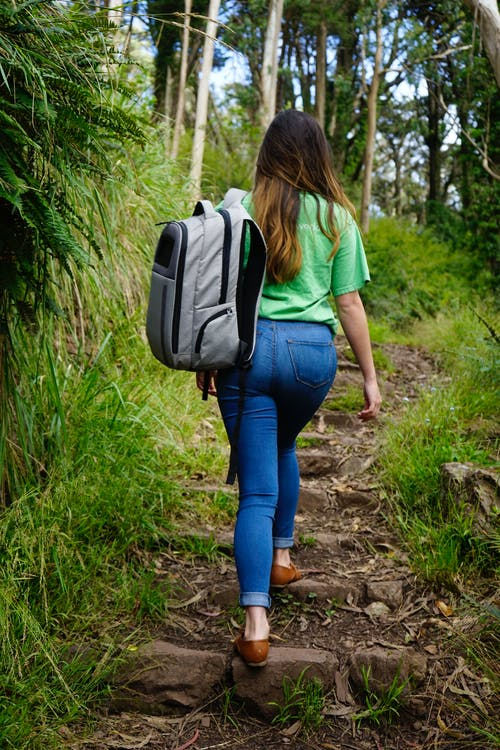 Woman in White T-shirt and Blue Denim Jeans Walking on Pathway Between Green Grass during