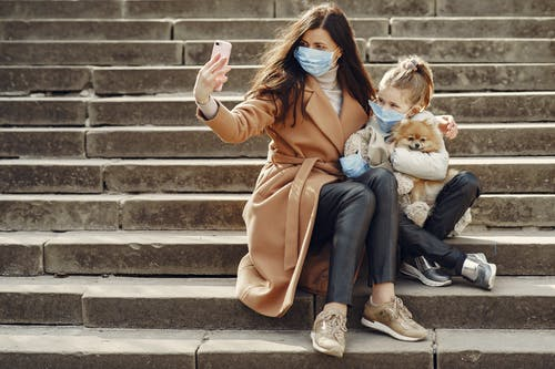 Young woman hugging cute daughter with dog in masks taking selfie on steps