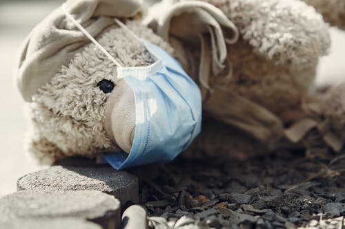 Lost teddy toy in protective mask lying on pavement alone