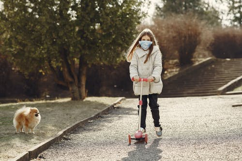 Full length of little girl in mask riding scooter while walking pet in nature