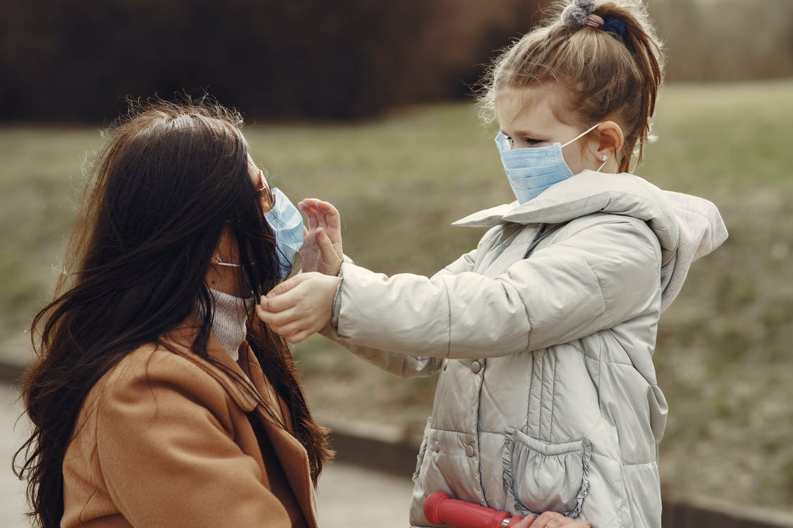 Cute little girl in mask helping put on medical mask for mom in sunglasses during stroll in park