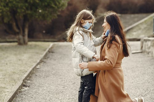 Loving mother and daughter wearing medical masks and spending time in park