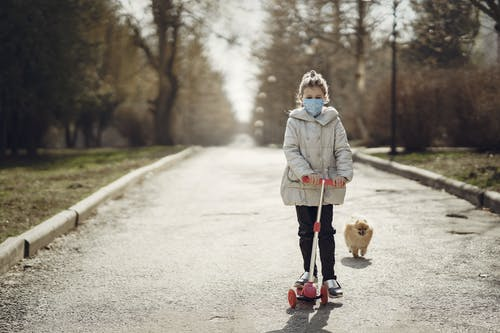 Kid in warm clothes using scooter while walking adorable dog in park