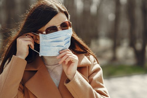 Woman in outerwear adjusting protective mask on face while walking in nature