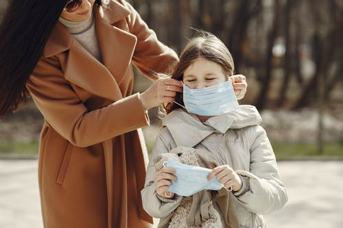Crop female helping to put on medical mask for daughter during stroll in nature