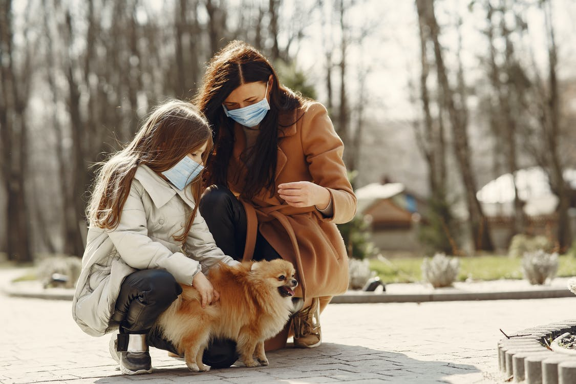 Cheerful daughter and mom in warm clothes and medical masks with little Pomeranian dog enjoying weekend in nature together