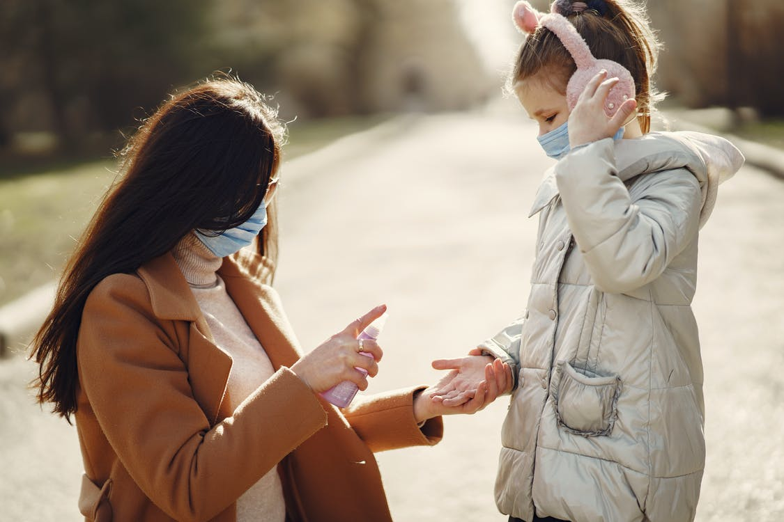 Caring mother spraying hands of daughter with antiseptic while walking in park