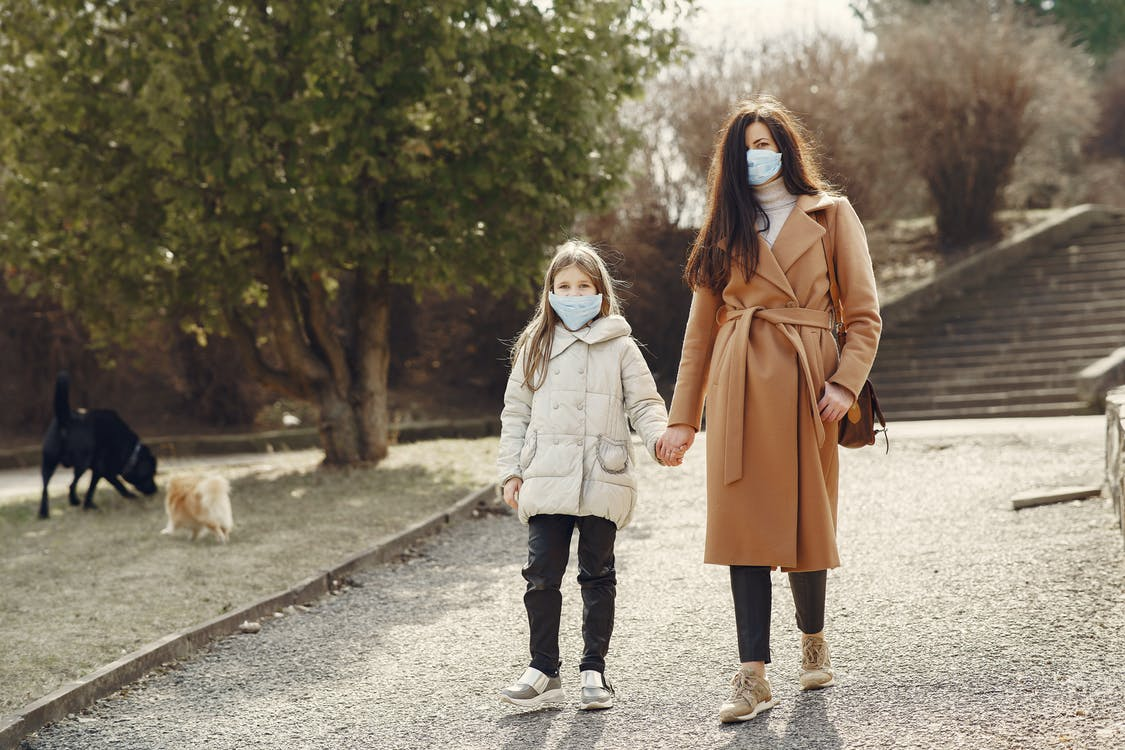 Mother with daughter in face masks walking in park