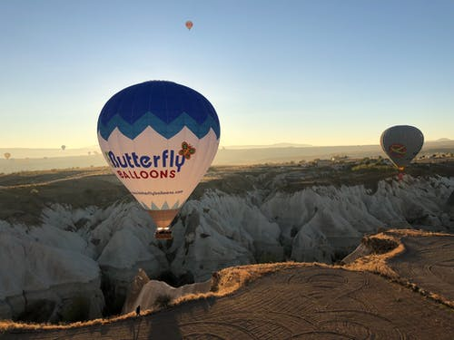 山の上に浮かぶ青と白の熱気球