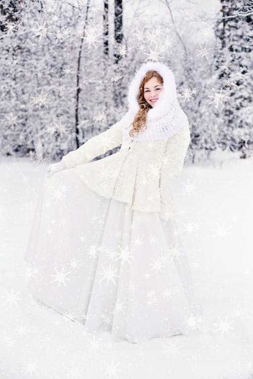 Woman in White Snow Suit Standing on a Snow Covered Ground Behind a Snow Covered Tree