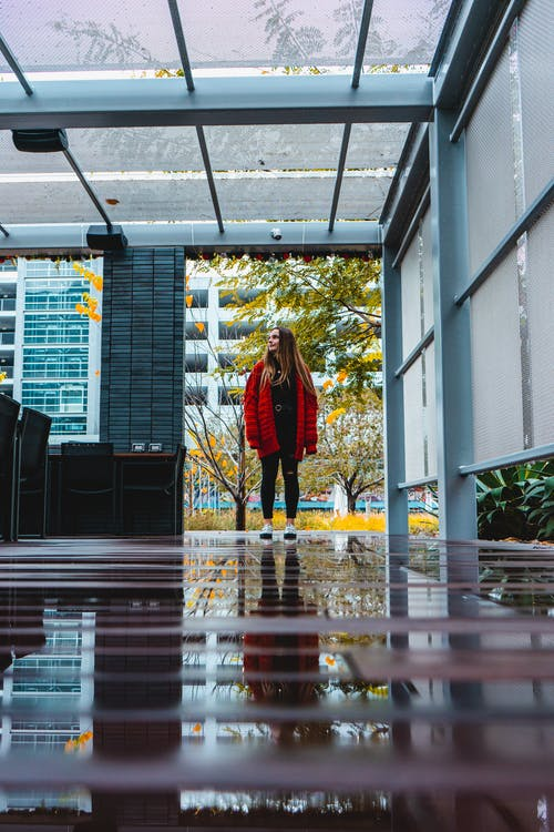 Unrecognizable woman standing in modern style building with shiny floor