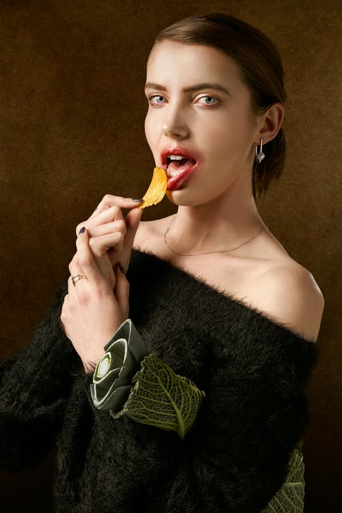 Woman In Black Top Holding A Potato Chip