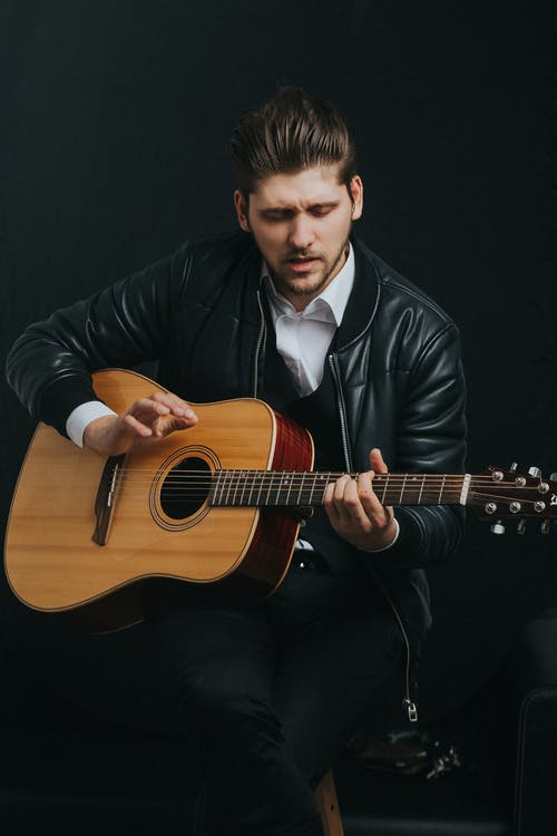 Man In Black Jacket Playing Brown Acoustic Guitar