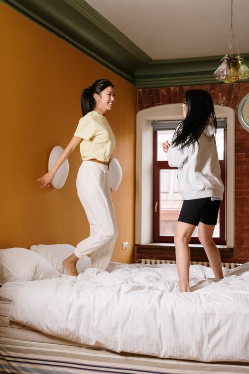 Woman in White Long Sleeve Shirt and Black Shorts Standing on Bed