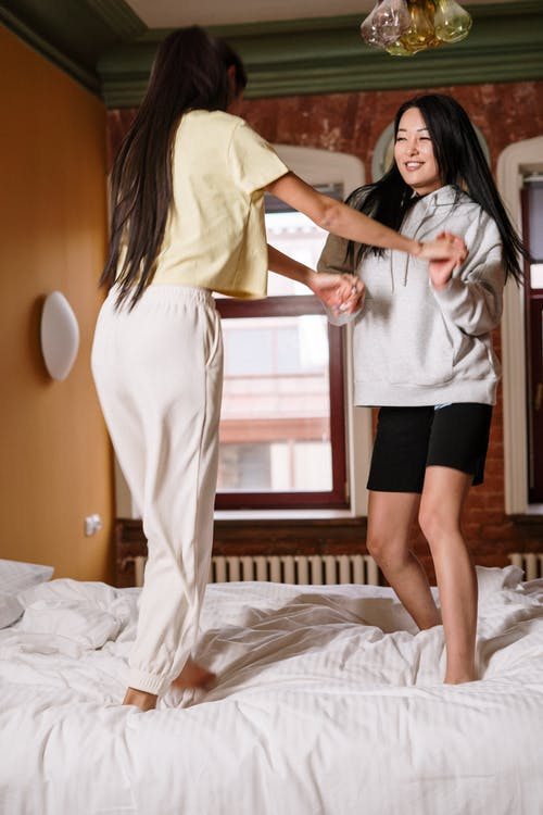 Woman in White Shirt and Black Skirt Standing on Bed