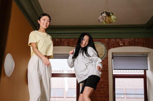 2 Women Standing Beside Window